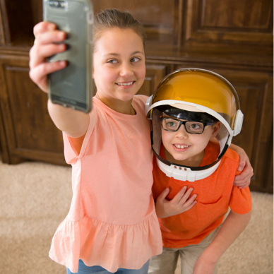 A child with Dravet syndrome taking a selfie with his sister