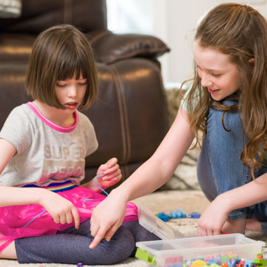 A child with Dravet syndrome working on a word puzzle with her sister