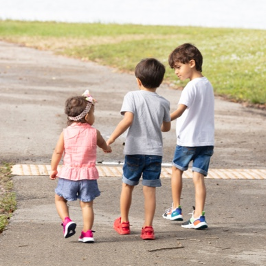 A child with Dravet syndrome walking with his brother and sister